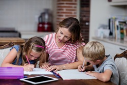 Mother helping kids with their homework at home