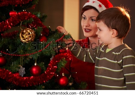 Mother helping little boy to decorate christmas tree at home.?