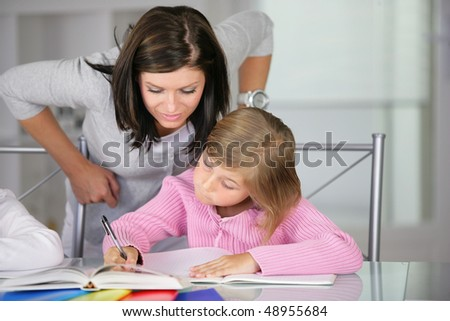 Mother helping little girl to do homework