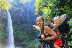 Mother hold baby girl on back in carrying backpack walking in waterfall canyon. Travel adventure and hiking activity with child, active and healthy lifestyle on family summer vacation and weekend tour