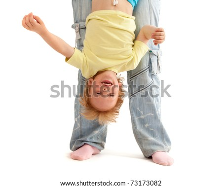 Mother hold her smiling son upside down. Isolated on white