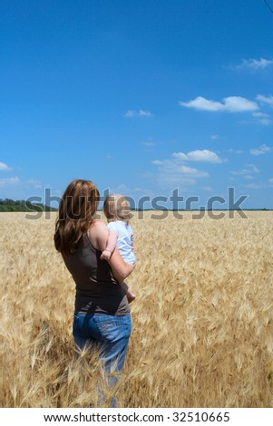 mother holding a child at the wheat field
