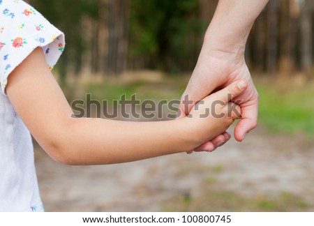 Mother holding a hand of her daughter  in spring day outdoors #100800745