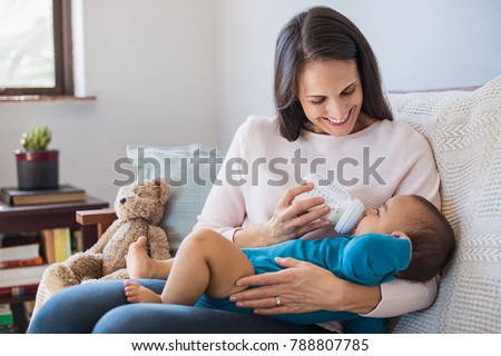 Mother holding and feeding baby from milk bottle. Portrait of cute newborn baby being fed by her mother using bottle. Loving woman giving to drink milk to her son.