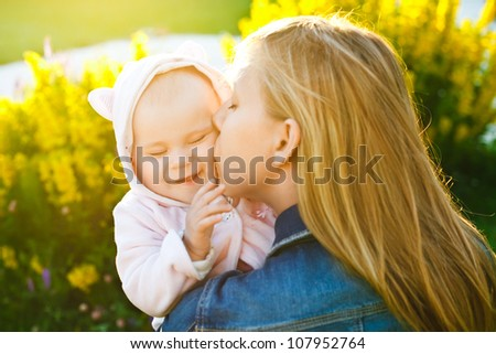 mother holding and kissing her little daughter outdoors in sunlight