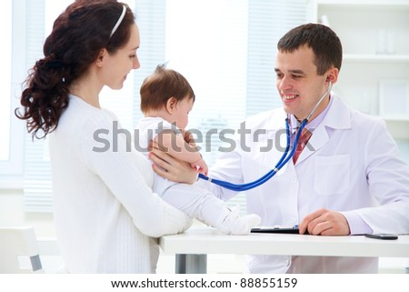 Mother holding baby for pediatrician to examine