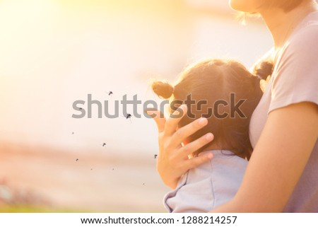 Mother holding baby girl in the park.Little girl has allergies with mosquitoes bite.Mother protection kid.Mosquito blood breeding on kids.Repellent, Dengue virus, Yellow fever, West nile, Malaria.