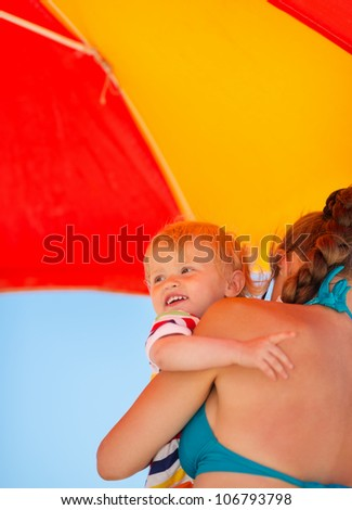 Mother holding baby looking on copy space on beach under umbrella