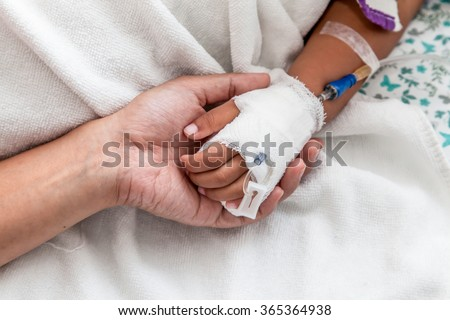 Mother holding child's hand who have IV solution in the hospital