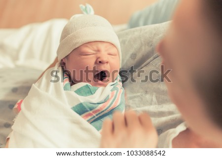 Mother holding cute newborn baby boy in her arms. Sleepy baby yawning.