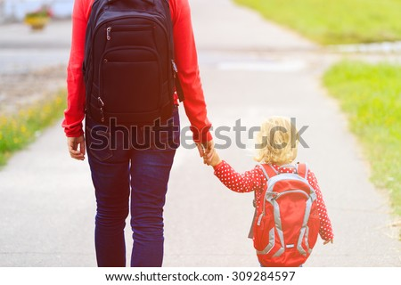 Mother holding hand of little daughter with backpack going to school or daycare - stock photo