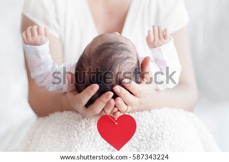 Mother holding head of her newborn baby in hands. Happy family concept. Maternal love and parental love.  Red heart hanging from the arms.