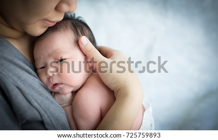 Mother holding her newborn baby daughter after birth on arms.,  Concept of love and family., Newborn baby girl., new life.