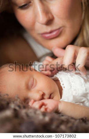 Mother holding her newborn baby, selective focus on baby