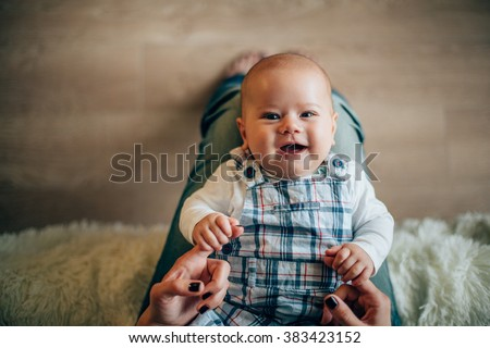 Mother holding her smiling newborn son in hands