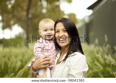 Mother holding Little Baby in front of tall grass at the Park