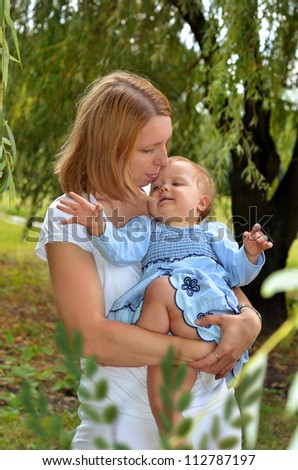 mother holding on hands her sweet baby girl in blue dress in the park