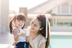 Mother holding sun screen cream tube with her daughter near swimming pool.Happy mother applying sun cream to little adorable kid girl.Sunscreen or sunblock and Skincare concept.