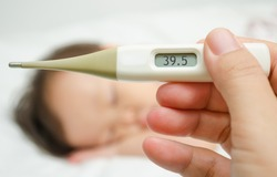 Mother holding thermometer foreground and sick little girl in be