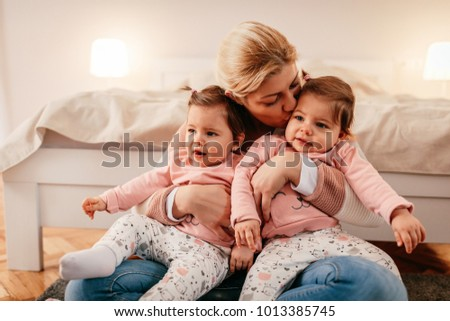 Mother holding two baby girls