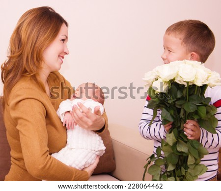 Mother holds cute baby, gift flowers for my mom
