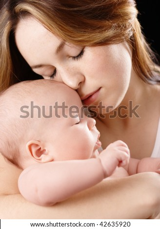 Mother holds her dreaming child, isolated over black