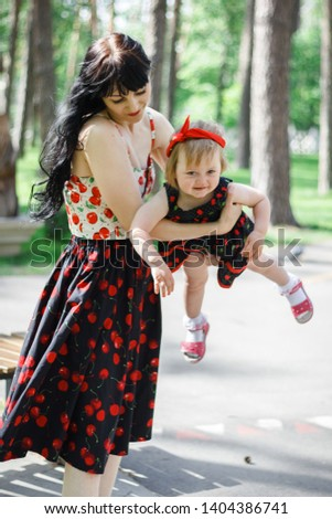 Mother holds little lovely smiling daughter at her hands. Spring park. Childhood. Concept of a happy family. Mother and kid. Universal Children's Day.. #1404386741
