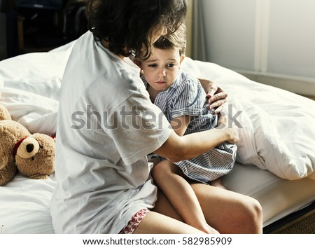 Mother hug and consoling the little boy from nightmare