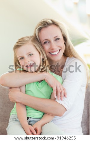 Mother hugging her daughter on the couch