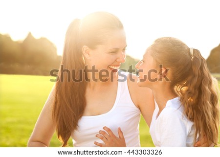Mother hugging with her little daughter outdoor in nature on sunny day. Sunset #443303326