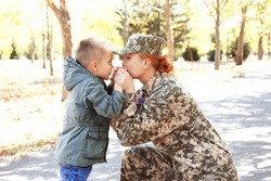 Mother in army uniform meeting her son in park