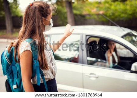 Photo of  Mother in car, dropping off her daughter to the school and wishing her a good day. Back to school, motherhood concept.