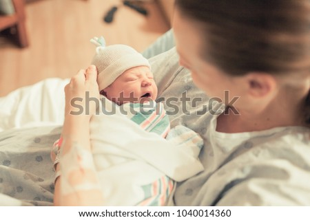 Mother in hospital holding her new born baby boy. Birth and new life.