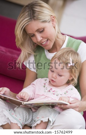 Mother in living room reading book with baby smiling