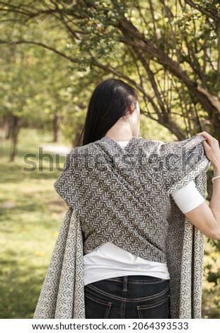 Mother in the forest preparing to carry her baby in a sling