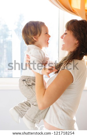 Mother in white clothes holding little son against window
