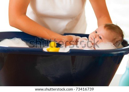 Mother is bathing her baby (just hands)
