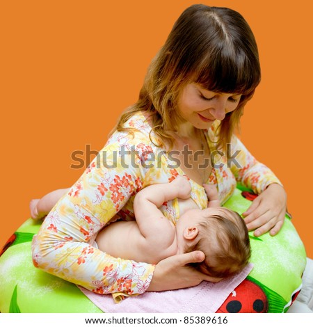 Mother is breast-feeding a newborn baby. Isolated on orange background with clipping path