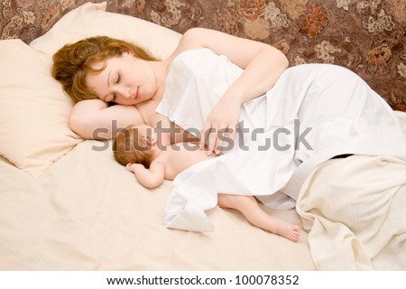 Mother is breast feeding a newborn baby lying down in bed. The symbol of happiness and motherhood