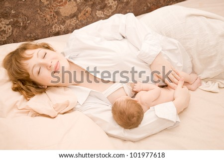 Mother is breast feeding a newborn baby lying down in bed. The symbol of happiness and motherhood. Lucky family is sleeping.