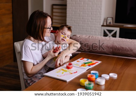 Mother is engaged in rehabilitation with a disabled kid. Development by creativity. drawing lesson with cerebral palsy. Happy childhood of a child with special needs. Art therapy. Stock photo ©