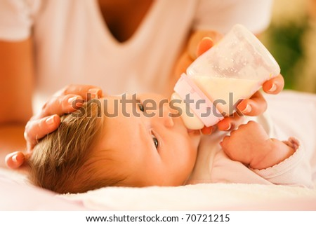 Mother is feeding her baby with a bottle; very tranquil scene