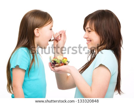 Mother is feeding her daughter with fruit salad, isolated over white