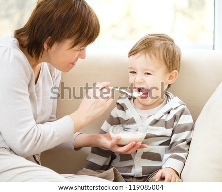 Mother is feeding her son while sitting on a couch