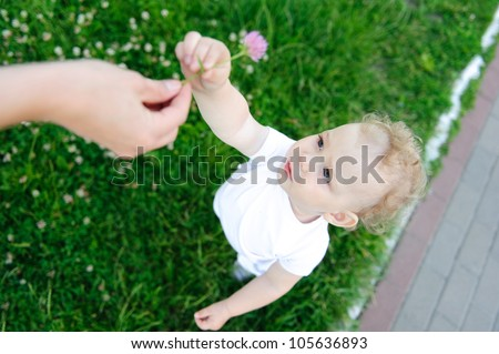 Mother is giving a flower to her little daughter