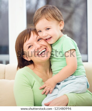 Mother is having fun with her son while sitting on a couch