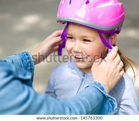Mother is helping her daughter with safety helmet outdoors
