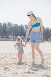 Mother is holding child's hand on the sandy beach near ocean in sunny day