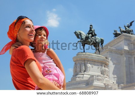 Mother is holding little daughter, equestrian monument to Victor Emmanuel II near Altar of fatherland in Rome, Italy