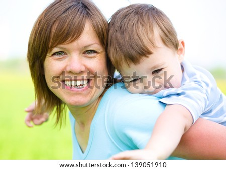 Mother is playing with her son outdoors